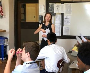 Ms. Steinmeyer distributes papers to her sophomore English class as they study