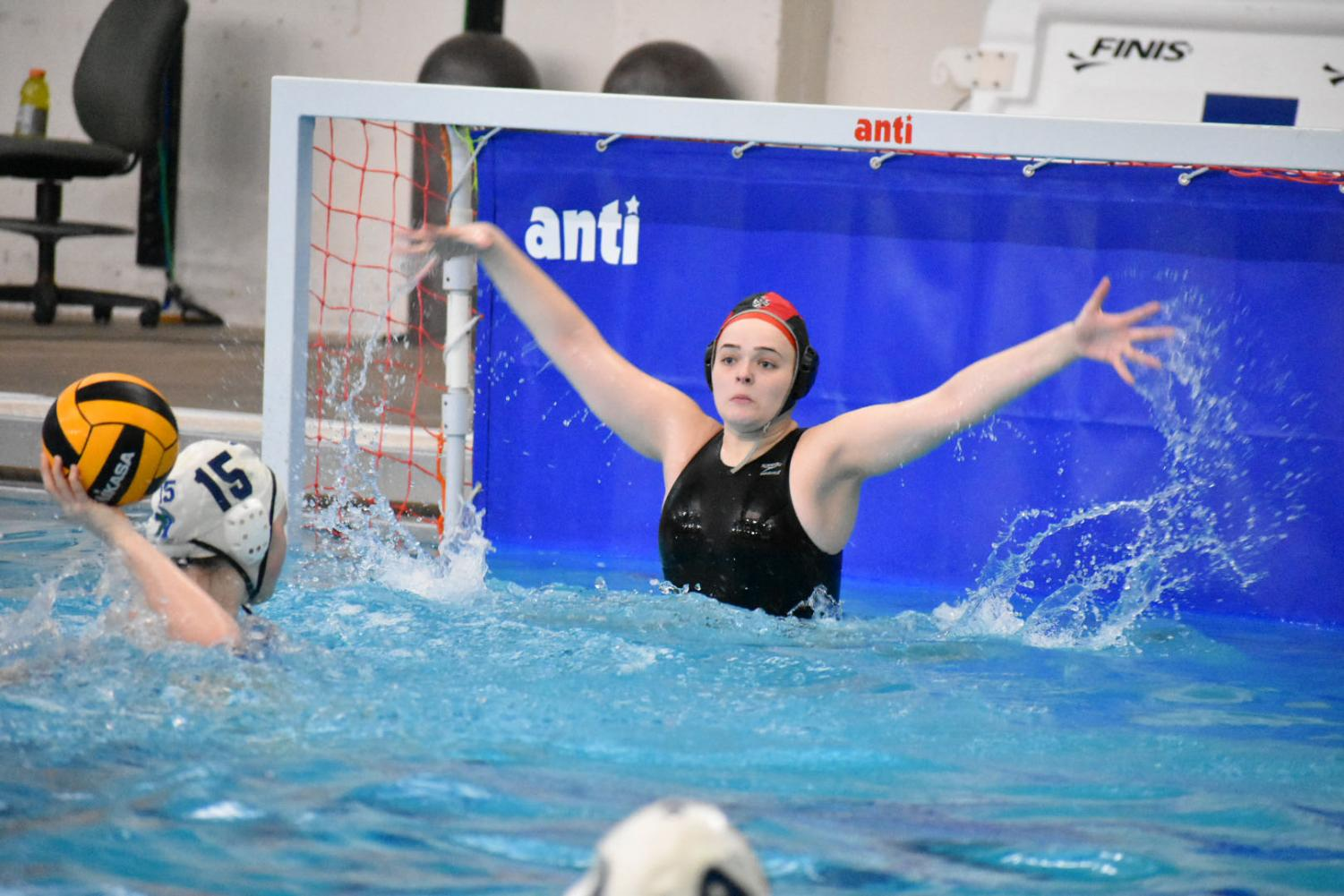 Junior Peyton Nufer jumps to block a shot during an intense water polo game.  Photo by Demi Ovalle